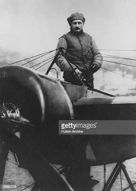 French pioneer and air ace Roland Garros standing above the wirebraced wing of his MoraneSaulnier which would fire bullets from the propeller