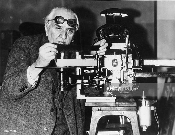 French pioneer filmmaker Louis Lumiere in Paris with projecting apparatus for his new anaglyph stereoscopic film system 3rd July 1935 He is wearing...