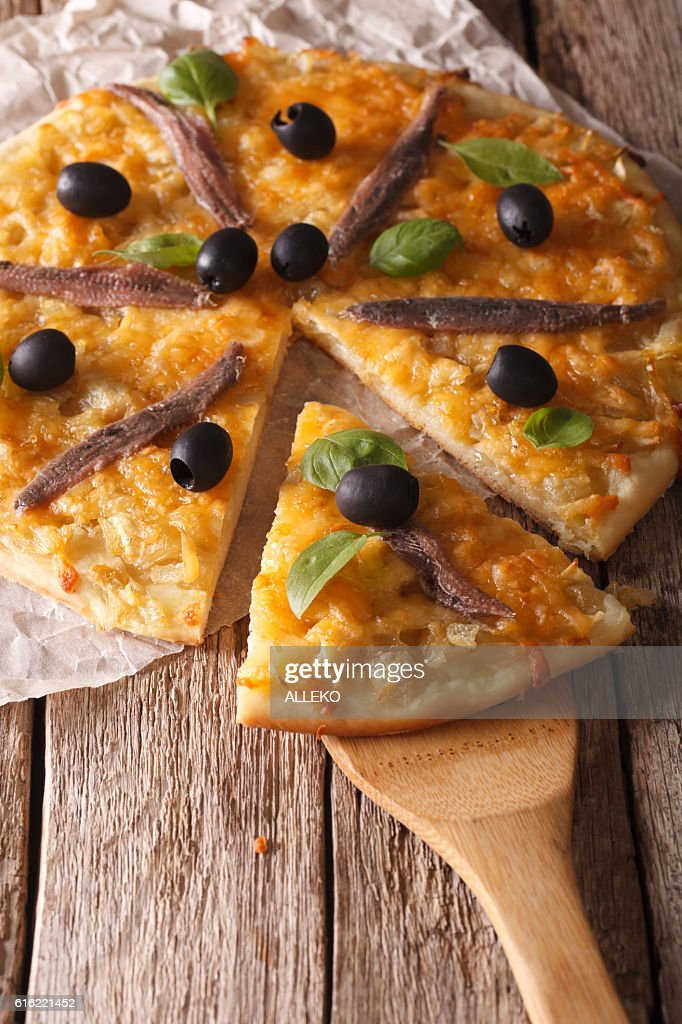 French Pissaladiere with anchovies and onions close-up. Vertical : Stock Photo