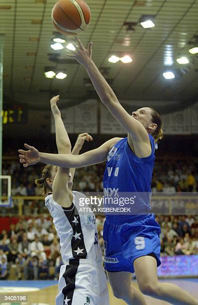 French player Audrey Sauret of Valenciennes Olympic scores a basket beside her Hungarian opponenet Albena Branzova of MizoPVSK 16 April 2004 after a...