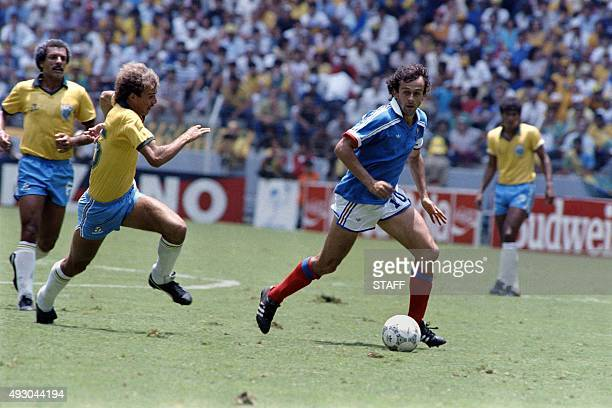 French player Michel Platini fights for the ball against his Brazilian opponents Alemao and Junior , during the World Cup football match between...