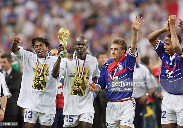 French players Bernard Diomede, Lilian Thuram, Didier Deschamps and Thierry Henry celebrate after receiving the 1998 FIFA trophy 12 July at the Stade...
