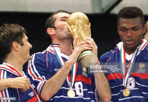 French players Bixente Lizarazu and Marcel Desailly watch midfield mastermind Zinedine Zidane kissing the World Cup trophy during the awards ceremony...
