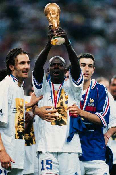 French players Christophe Dugarry, Lilian Thuram, and Robert Pires celebrate with their trophy after winning the 1998 FIFA World Cup 3-0 against...