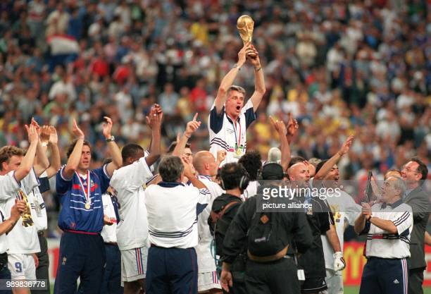 French players jubilate with the World Cup and their upheaved coach Aime Jacquet after France wins the 1998 World Cup final against defending champs...