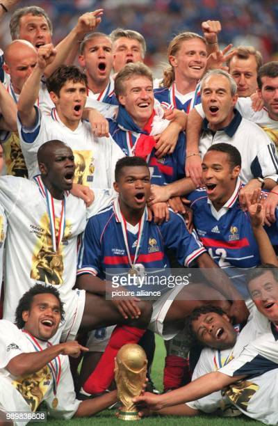 French players surrounding team captain Didier Deschamps and head coach Aime Jacquet jubilate with the World Cup trophy in front of them after the...