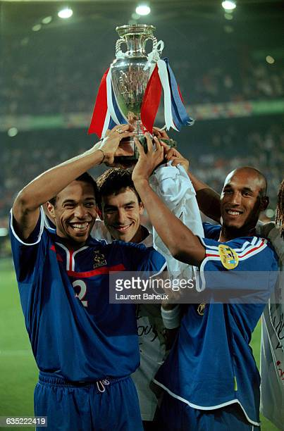 French players Thierry Henry, Robert Pires and Nicolas Anelka celebrate victory, holding their trophy high, following the 2000 UEFA European...