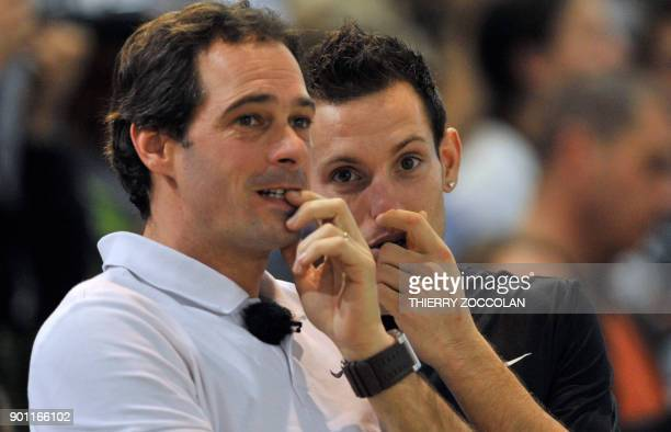 French pole vault champion Renaud Lavillenie speaks with his coach Damien Inocercio during the French Indoor Athletic Championships in Aubiere...