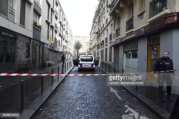 French police are seen behind a police cordon at the Rue des Islettes near BarbesRochechouart metro station in the north of Paris on January 7 after...
