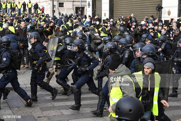 French police charge as demonstrators take part in the demonstration of the yellow vests near the Arc de Triomphe on December 8 2018 in Paris France...