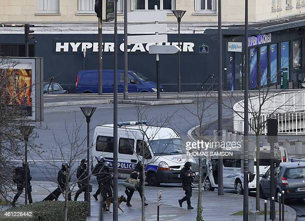 French police forces walk by the Hyper Cacher kosher grocery storein Porte de Vincennes eastern Paris where at least one person was injured when a...