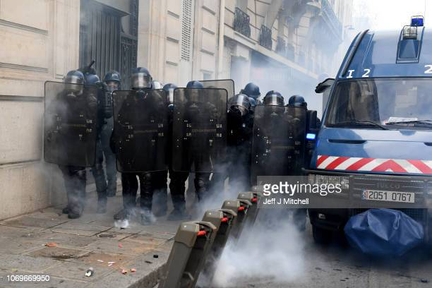 French police form a blockade surrounded by tear gas during the demonstration of the yellow vests near the ChampsElysees avenue on December 08 2018...