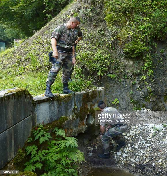 French police inspect a drain under the road to the murder scene at Cheverlaine near Annecy in the HauteSavoie region of southeastern France where...