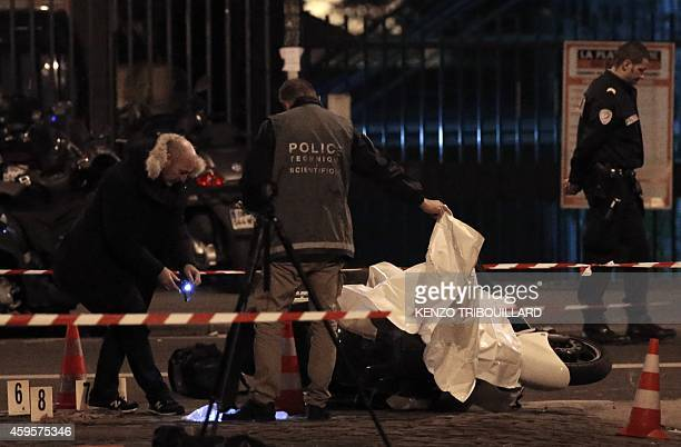 French police investigators gather evidence near a motor scooter in Paris' 15th arrondissement used by two alleged robbers who targeted a Cartier...