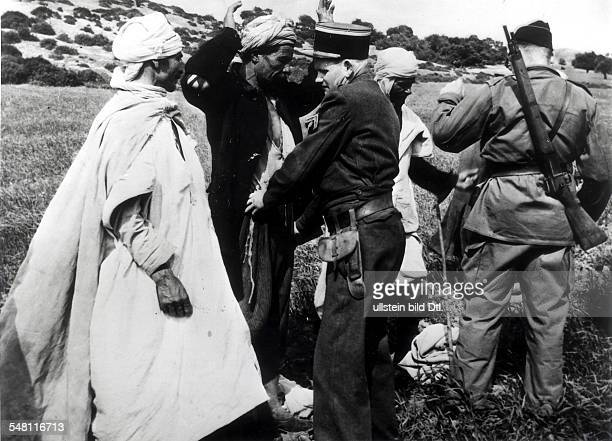 ALGERIAN WAR 1956 French police officer and soldier search civilians on the AlgiersTablat highway the scene of repeated attacks on passing vehicles...