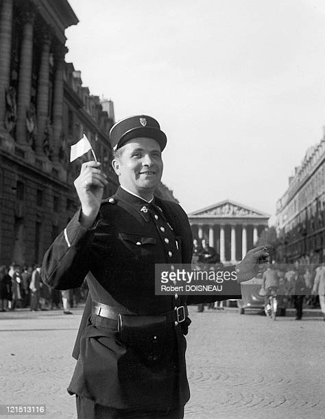 French Police Officer Brandishing The French Flag On The Day Of Armistice On Place De La Concorde In Paris On May 8Th 1945