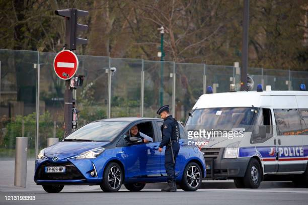 French police officer checks a driver in front of the Eiffel Tower the second day after the announcement by French President Emmanuel Macron of the...