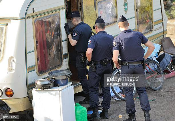 A French police officer enters a caravan as French police carry out identity checks at a Roma camp on October 1 2013 in Roubaix northern France...