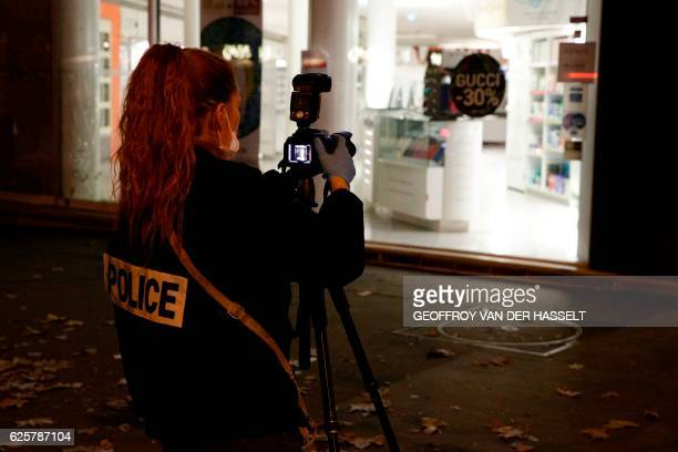 French police officer films with a camera outside the building where British photographer David Hamilton was found dead at his home on November 25 in...