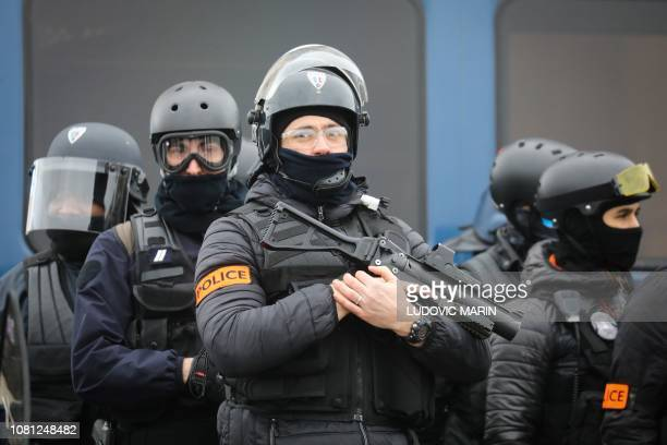 A French police officer holds a nonlethal handheld weapon during an antigovernment demonstration called by the Yellow Vest movement in Paris on...