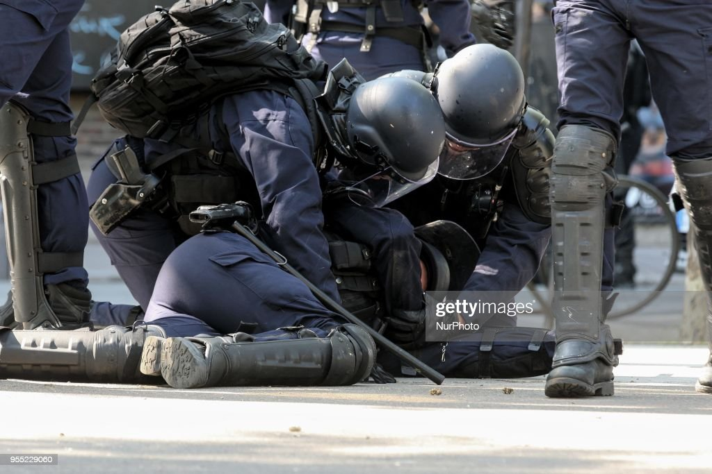 "A French police officer lies injured on the ground as thousands gathered during a protest dubbed a ""Party for Macron"" (Fete a Macron) against the policies of the French president on the first anniversary of his election, on May 5, 2018, in Paris."