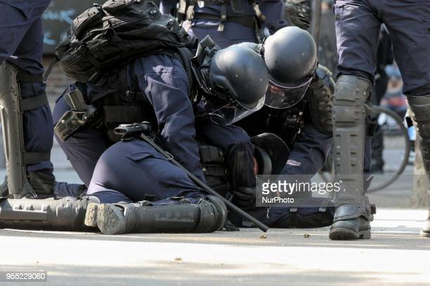 A French police officer lies injured on the ground as thousands gathered during a protest dubbed a quotParty for Macronquot against the policies of...