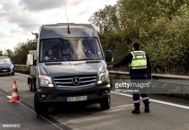 A French police officer shows a pickup where to drive as he stands on the highway A27 during a French and Belgian bilateral operation of control...
