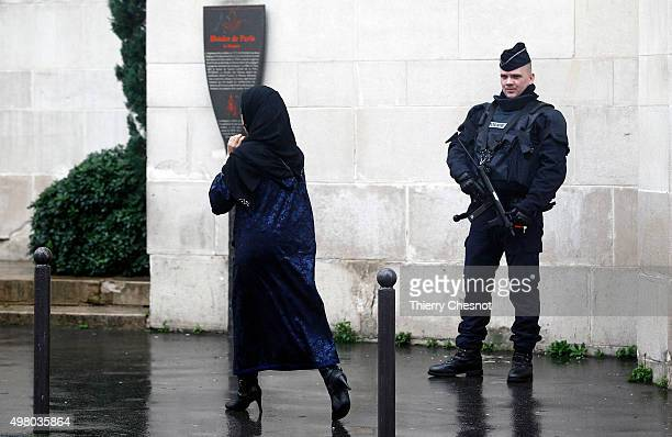 French police officer stands guard as a Muslim woman leaves the Great Mosque of Paris after the Friday prayers on November 20 2015 in Paris France...