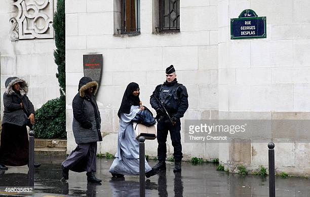 French police officer stands guard as Muslim women leave the Great Mosque of Paris after the Friday prayers on November 20 2015 in Paris France...