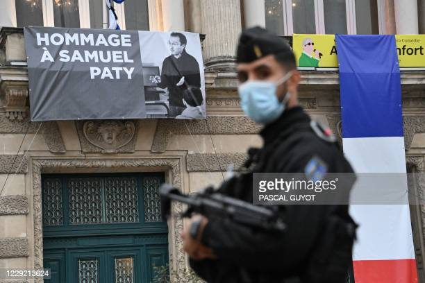 French police officer stands next to a portrait of French teacher Samuel Paty on display on the facade of the Opera Comedie in Montpellier on October...