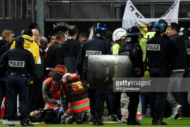 French police officers and members of the stadium staff stand by rescuers as they take care of wounded LOSC' supporters following the fall of their...