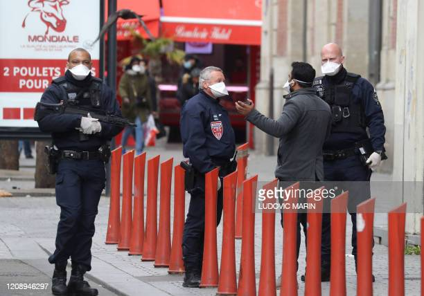 French police officers control people's outings authorisations on April 2, 2020 in Saint-Denis, near Paris, on the seventeen day of a lockdown aimed...