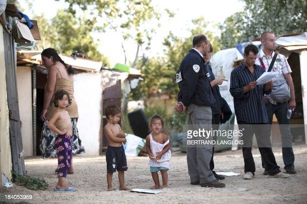 French police officers control the identity of people belonging to the Roma community on August 19 2010 in the camp site where they live in...