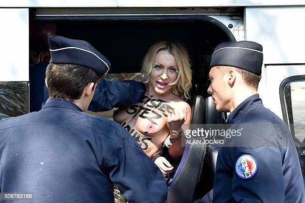 French police officers detain Femen activist Inna Shevchenko during a protest outside a banquet held by France's farright Front National party in...