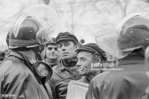French police officers in riot gear face protesting fishermen outside the Ministry for the Merchant Navy in Paris where the police are attempting to...