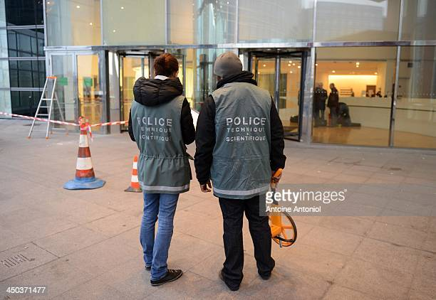 French police officers investigate outside the Societe Generale headquarters at La Defense business district following gun attack on November 18 2013...