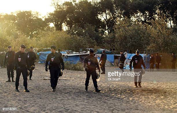 French police officers move through the makeshift migrant camp known as 'The Jungle' adjacent to a ferry terminal to the UK on September 22 2009 in...