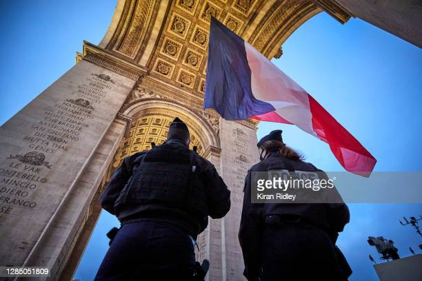 French Police officers observe the raising of the French Tricolor Flag above the Eternal Flame and the Tomb of the Unknown Soldier at the Arc de...