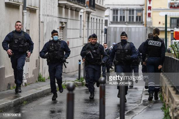 French police officers rush to the scene after people were injured near the former offices of the French satirical magazine Charlie Hebdo following...