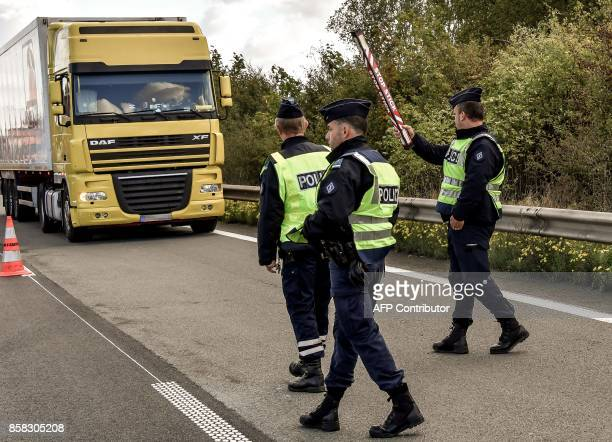 A French police officers show a truck where to drive as they stand on the highway A27 during a French and Belgian bilateral operation of control...
