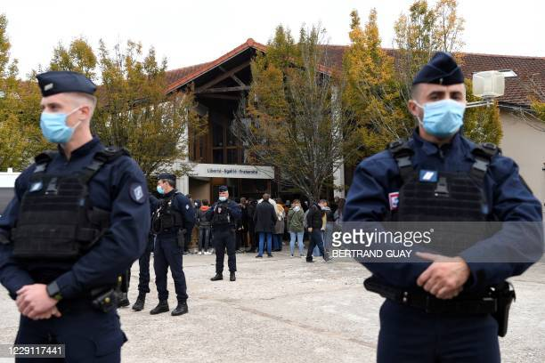 French police officers stand as adults and children gather in front of flowers displayed at the entrance of a middle school in...