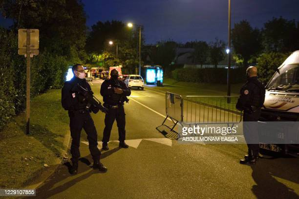 French police officers stand guard a street in Eragny on October 16 where an attacker was shot dead by policemen after he decapitated a man earlier...