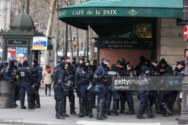 French Police officers stand guard in front the Café de la Paix at the place de l'Opera in front of the Opera Garnier in Paris on December 15 during...