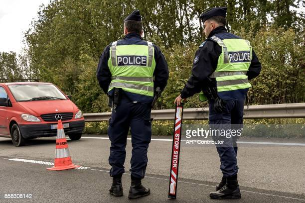 French police officers stand guard on the highway A27 during a French and Belgian bilateral operation of control conducted by the police and customs...
