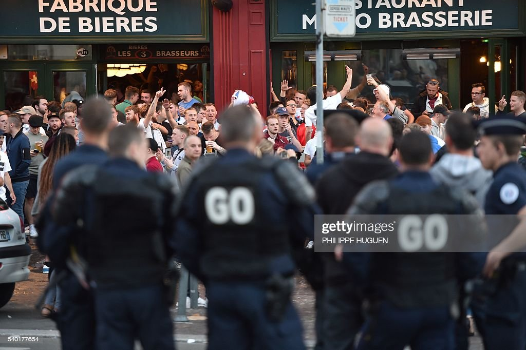 French police officers stand in front of footbal fans drinking beer at the terrace of a bar in Lille, northern France, on June 14, 2016. The bars in downtown Lille will be closed 'at midnight' on June 15 and 16, on the sidelines of the Euro 2016 football tournament matches Russia vs Slovakia in Lille and England vs Wales in Lens, has announced on June 14, 2016 the Prefect of the Nord region, Michel Laland. / AFP / PHILIPPE