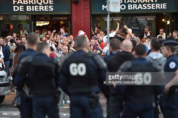 French police officers stand in front of footbal fans drinking beer at the terrace of a bar in Lille northern France on June 14 2016 The bars in...
