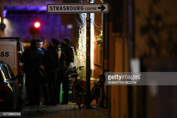 French police officers stand near the place where Cherif Chekatt the alleged gunman who had been on the run since allegedly killing three people at...