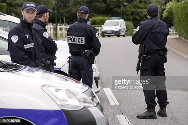 French police officers stand on June 14 2016 on the street in Magnanville where a man claiming allegiance to the Islamic State group killed a French...