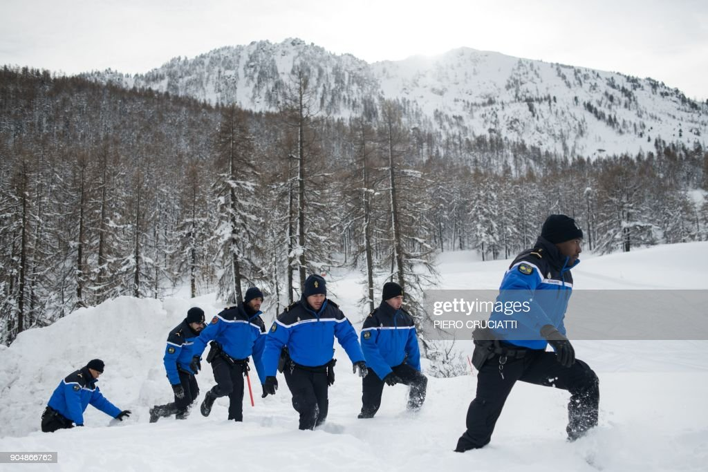 French police officers walk in high snow during the Briser les frontieres activist group march between Claviere, Italy and Montgenevre, France in support of migrants and to ask free movement between European countries in Cleviere , Italy, on January 14, 2018. / AFP PHOTO / Piero CRUCIATTI