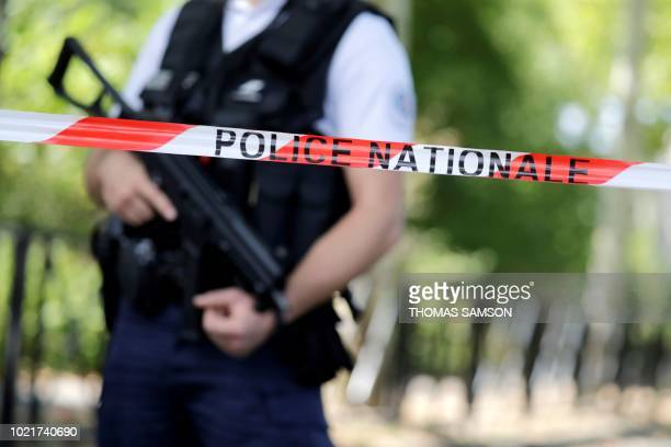 A French police official stands alert at a cordonedoff road in Trappes southwest of Paris on August 23 following a knife attack A man armed with a...